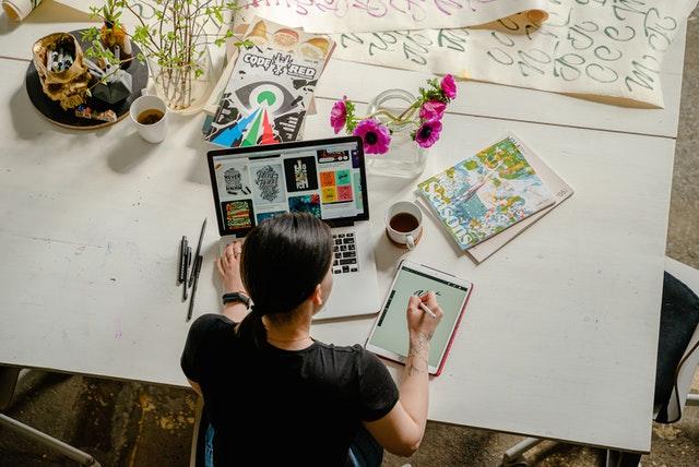 Nainen työskentelee tietokoneella ja tabletilla