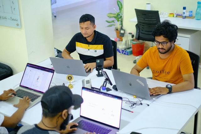 Suunnittelijoita työssään tietokoneilla pöydän ääressä
