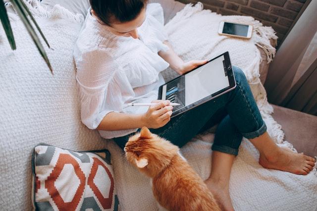 Nainen työskentelee sohvalla tabletilla